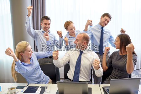 business people celebrating victory in office