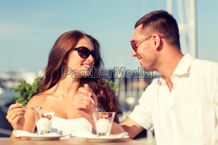 smiling couple eating dessert at cafe