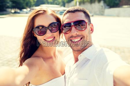 smiling couple wearing sunglasses making selfie