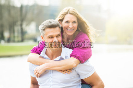 happy man piggybacking his wife