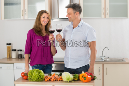 portrait of happy couple toasting red