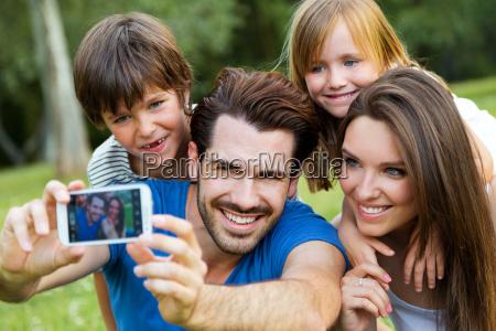 glueckliche junge familie die selfies mit