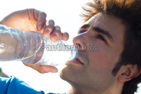 man drinking water after sport activities