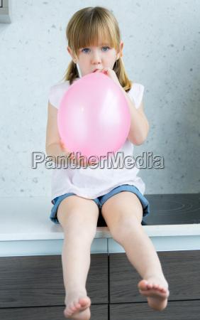 nettes kleines maedchen aufblasen einen rosa