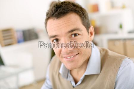 smiling man sitting at desk in