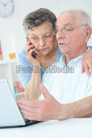 elderly couple using laptop wife on
