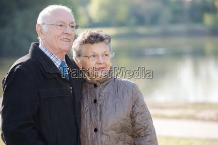elderly couple beside a lake