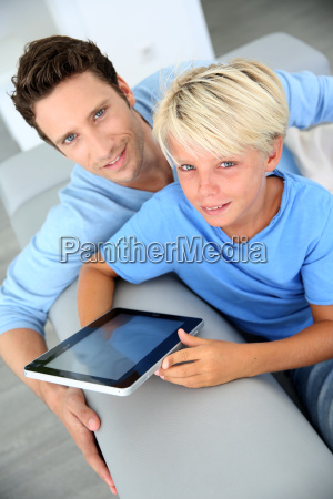father and son using digital tablet