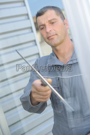 man cleaning a glass window
