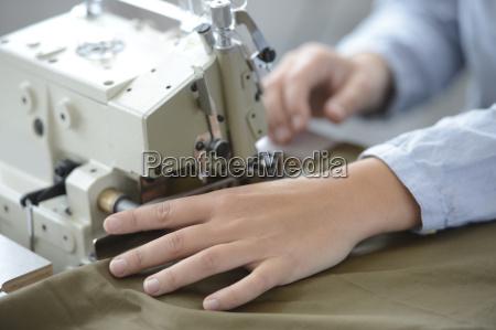 closeup on dressmaker hand using sewing