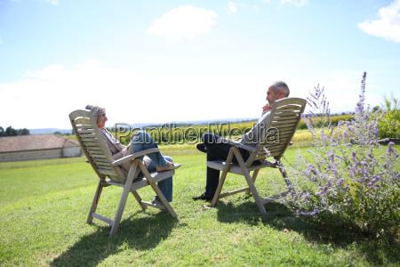 senior people relaxing in long chairs