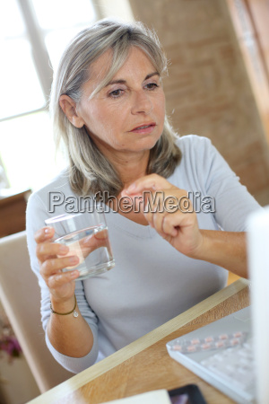 senior woman reading medication instructions on