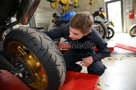 jugendlicher in der berufsausbildung reparatur motorrad