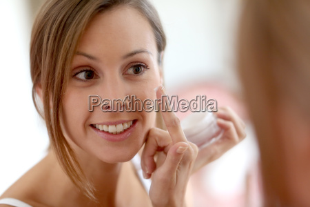 young woman applying anti wrinkles cream