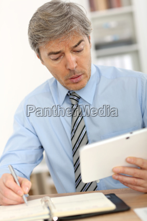 senior manager in office using tablet