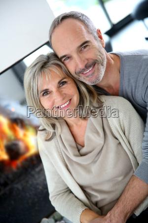 cheerful senior couple enjoying fireplace in