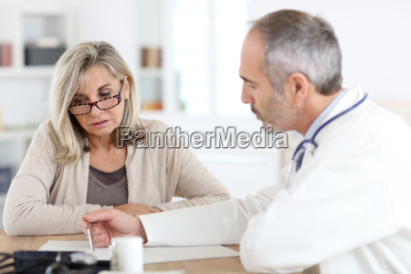 doctor giving medicine to senior woman