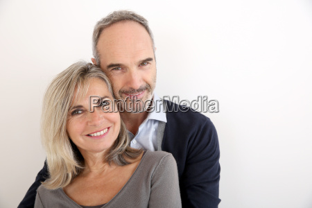 cheerful senior couple standing on white