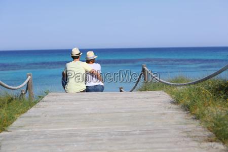 rueckansicht der paar entspannenden am strand