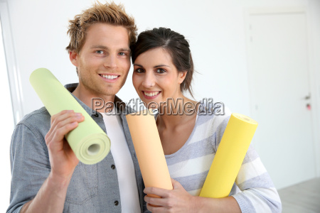 portrait of smiling couple holding wallpaper
