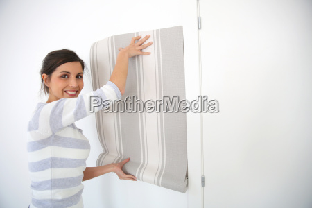 young woman choosing wallpaper for new