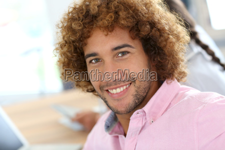 cheerful man in office attending work