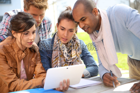 group of students using tablet outside