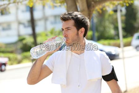athletischer mann trinkwasser nach dem sport