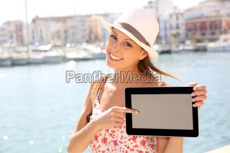 schoene touristische maedchen zeigt tablet bildschirm