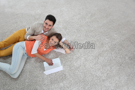 couple laying on carpet of brand