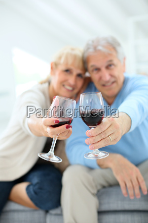 cheerful senior couple cheering with glass