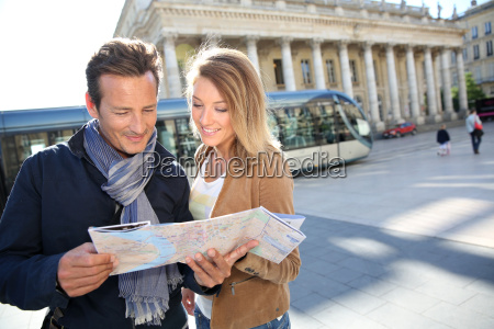 cheerful couple in bordeaux reading city