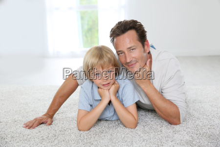 father and son laying on carpet