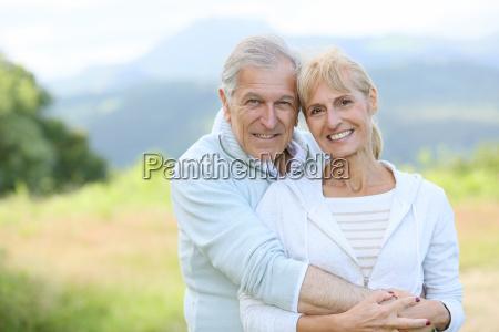portrait of cheerful senior couple embracing