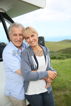 senior couple standing by motorhome in