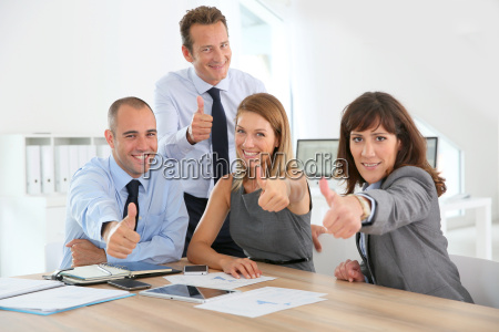 cheerful business team showing thumbs up