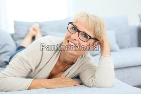 laechelnde aeltere frau mit brille auf
