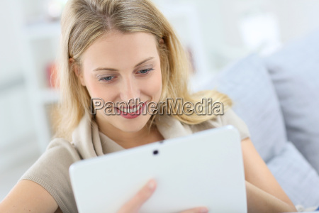 blond woman at home using digital