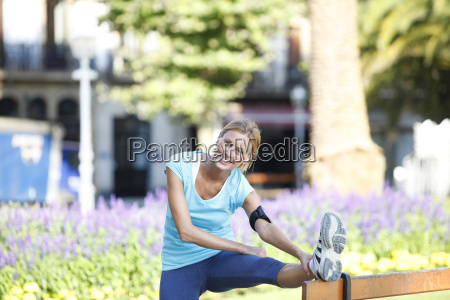 fitness girl stretching legs after running