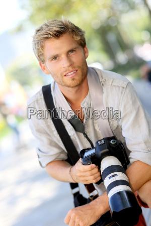 portraet von huebschen fotografen mit kamera