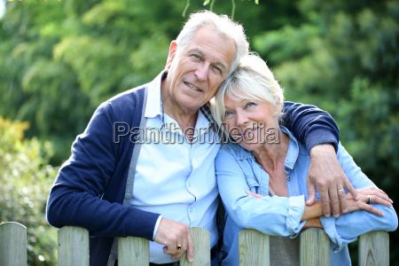 senior couple standing by fence in