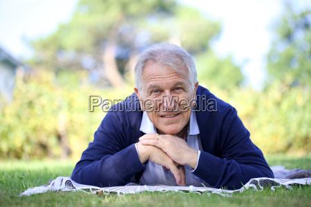 senior man laying in garden and