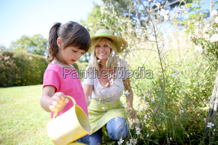 woman with little girl watering plants