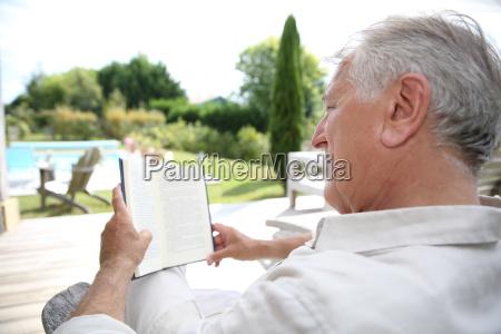 senior man reading book in pool