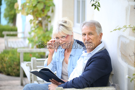 senior couple reading book outside their