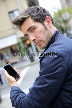 man in city street showing smartphone