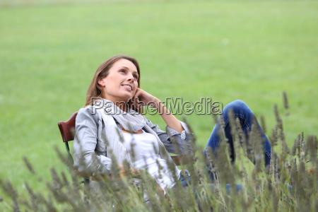 frau entspannt im stuhl im hausgarten