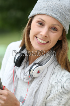trendy young woman in park listening