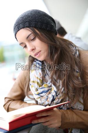 student girl reading book outside school