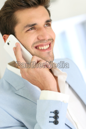 smiling attractive young man talking on